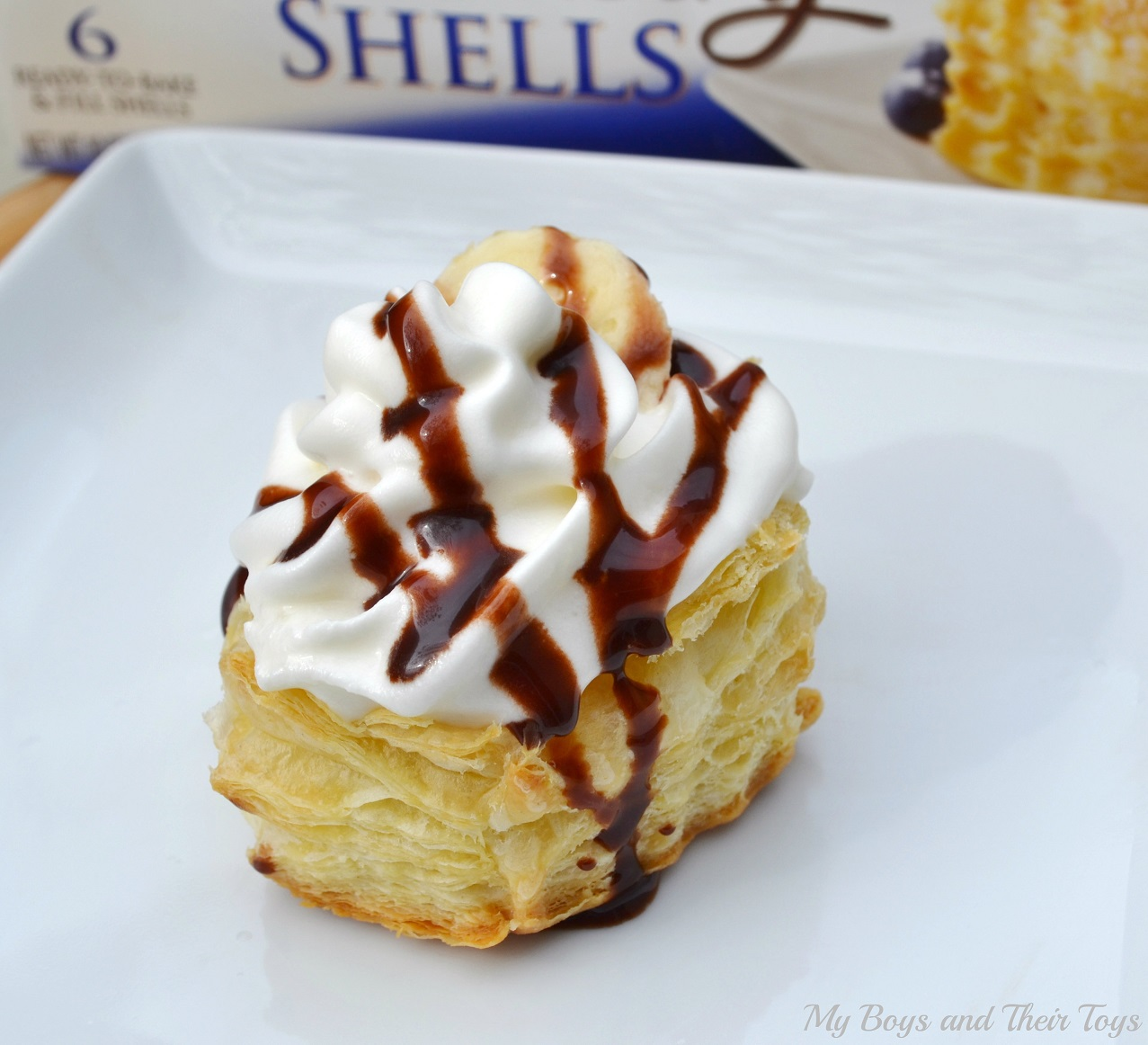 banana cream puffs with chocolate drizzle on white plate